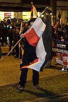 Ca. 90 Hooligans und Nazis beteiligten sich am Montag den 1. Februar 2016 im Berliner Stadtteil Prenzlauer Berg an einer NPD-Demonstration gegen Asyl und Fluechtlinge. Die aggressive Demonstration wurde von lautstarken Protesten mehrerer hundert Gegendemonstranten begleitet. Die Demonstrationsroute wurde auf Anweisung der Polizei um 2/3 gekuerzt.<br /> Im Bild: Ein vermummter Demonstrationsteilnehmer versteckt sich hinter seiner Fahne.<br /> 1.2.2016, Berlin<br /> Copyright: Christian-Ditsch.de<br /> [Inhaltsveraendernde Manipulation des Fotos nur nach ausdruecklicher Genehmigung des Fotografen. Vereinbarungen ueber Abtretung von Persoenlichkeitsrechten/Model Release der abgebildeten Person/Personen liegen nicht vor. NO MODEL RELEASE! Nur fuer Redaktionelle Zwecke. Don't publish without copyright Christian-Ditsch.de, Veroeffentlichung nur mit Fotografennennung, sowie gegen Honorar, MwSt. und Beleg. Konto: I N G - D i B a, IBAN DE58500105175400192269, BIC INGDDEFFXXX, Kontakt: post@christian-ditsch.de<br /> Bei der Bearbeitung der Dateiinformationen darf die Urheberkennzeichnung in den EXIF- und  IPTC-Daten nicht entfernt werden, diese sind in digitalen Medien nach §95c UrhG rechtlich geschuetzt. Der Urhebervermerk wird gemaess §13 UrhG verlangt.]