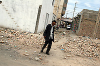 A man stands in the ruins of destroyed homes being modernised in the centre of town. Dunhuang, Gansu Province. China