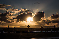 Masked by clouds, the sun casts a spotlight on visitors to the exercise stations along the shores of San Francisco Bay, creating silhouettes of people in motion.