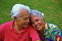 Affectionate senior Hawaiian man and part-Hawaiian woman with flower in her hair
