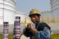 A worker walks past the oil tanks in Zhenhai national strategic oil reserve base, one of four national strategic oil reserve bases which started construction in 2003, in Ningbo, Zhejiang province, China. .