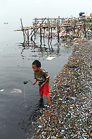 A young child playing by the shore in the bay of Jakarta.<br /> <br /> To license this image, please contact the National Geographic Creative Collection:<br /> <br /> Image ID: 1588018 <br />  <br /> Email: natgeocreative@ngs.org<br /> <br /> Telephone: 202 857 7537 / Toll Free 800 434 2244<br /> <br /> National Geographic Creative<br /> 1145 17th St NW, Washington DC 20036