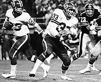 Ron Lancaster Saskatchewan Roughriders quarterback hands the ball to running back Pete Van Valkenburg 1976. Copyright photograph Scott Grant
