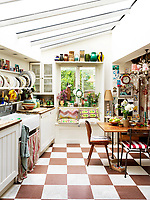 The cosy kitchen features a small window seat and a table with mismatched chairs and is decorated with family memorabilia