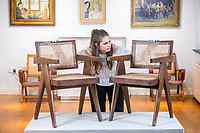 BNPS.co.uk (01202 558833)<br /> Pic: MaxWillcock/BNPS<br /> <br /> Pictured: Victoria Wild with the Chandigarh furniture, in the saleroom at Duke's in Dorchester, Dorset.<br /> <br /> Retro Indian chairs once consigned to the scrapheap are now tipped to sell for thousands of pounds after the style of furniture was endorsed by the Kardashians.<br /> <br /> The value of the distinctive solid teak chairs has sky-rocketed in recent years after ones like them were used to adorn the home of influencers like Kim and Khloe Kardashian.<br /> <br /> They were originally designed by Swiss architect Pierre Jeanneret to furnish public buildings of one of India's first modern cities in the 1950s.