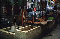 Canton  un cinese dorme vicino a un lavatoio nel mercato degli animali 1986<br /> a Chinese sleeping near a wash in the animal market
