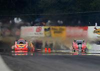 Oct. 6, 2012; Mohnton, PA, USA: NHRA funny car driver Cruz Pedregon (right) races alongside Jim Head during qualifying for the Auto Plus Nationals at Maple Grove Raceway. Mandatory Credit: Mark J. Rebilas-