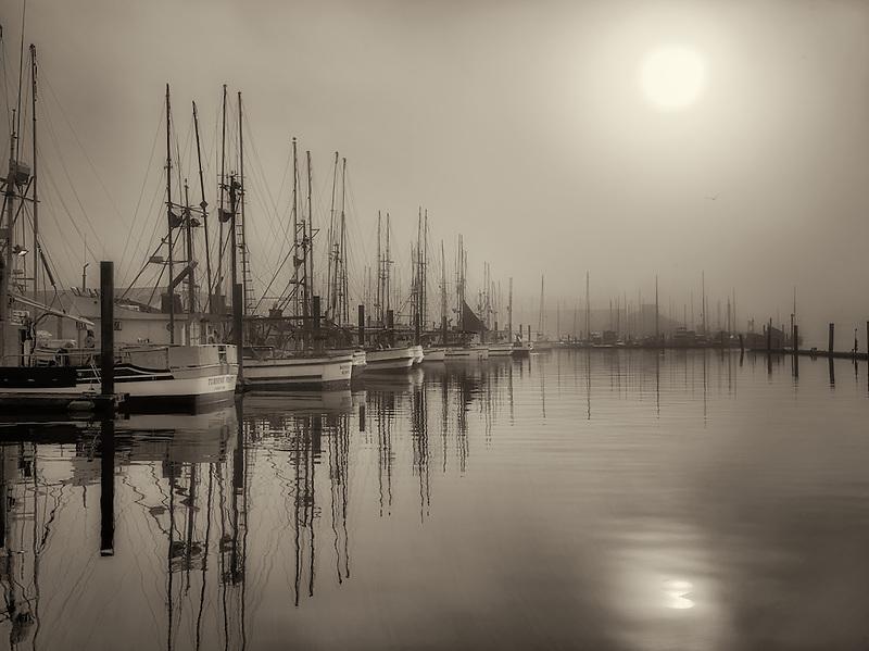 Sunrise through fog with boats at Newport Harbor. Oregon