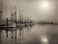 Sunrise through fog with boats at Newport Harbor. Oregon