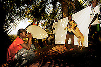 11 year old Rita want to become a photographer. Here she is taking a picture of her dog. She lives in a small village near Monrovia, the capital. .