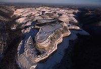Mountaintop Removal Mine in Winter<br /> Snow accentuates the contours of a freshly made valley fill in southwestern W.V. at Cantenary Coal near Cabin Creek. Mountaintop removal/valley fill is a mining practice where the tops of mountains are removed to expose the seams of coal. <br /> A much as 500 feet or more of a mountain summit may be leveled. The earth and rock from the mountaintop is then dumped in the neighboring valleys. Over 1,000 miles of streambeds are buried equaling the entire length of the Ohio River.