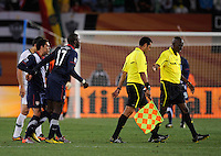 Jozy Altidore is held back by team-mate Herculez Gomez of USA as he tries to confront referee Koman Coulibaly