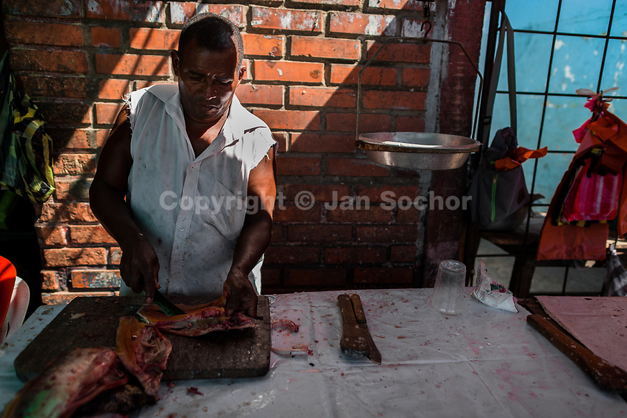 An Afro-Colombian fish vendor cuts fish in the market of Bazurto in Cartagena, Colombia, 16 December 2017. Far from the touristy places in the walled city, a colorful, vibrant labyrinth of Cartagena's biggest open-air market sprawls to the Caribbean seashore. Here, in the dark and narrow alleys, full of scrappy stalls selling fruit, vegetables and herbs, meat and raw fish, with smelly garbage on the floor and loud reggaeton music in the air, the African roots of Colombia are manifested.