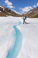 Man backpacking on aufies along the kuyuktuvuk creek drainage, Brooks Range, Gates of the Arctic National Park, Alaska.
