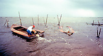 Andy Quick, of Eastpoint, Florida, empties water from his still floating oyster boat as Hurricane Juan brushes the Florida panhandle coast October 31, 1985.  Juan was the costliest hurricane of the 1985 season that also saw Danny and Elena.  Juan made landfall near the Florida-Alabama border.