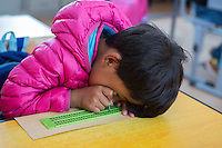 A visually impaired Tibetan student writes braille with the slate and stylus during a lesson at the School for the Blind in Tibet, in the capital city of Lhasa, September 2016.