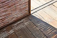 Bamboo blinds cast a textured shadow over the rough wooden flooring of the living area