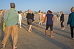 Men and women follow dance exercise teacher in movements on the beach at sunset.in Playa del Rey, California