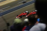 Michael Schumacher (#1-Ferrari) out brakes teammate Rubens Barrichello (#2-Ferrari) for the lead into turn one.