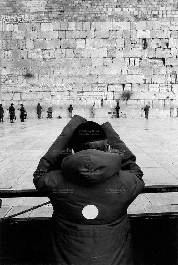 Israel. Jerusalem. Old city. Several Jewish men and a young boy wearing a kipper are praying at the Western Wall. A kippah (also spelled as kippa, kipa, kipah, kippot) is a brimless cap, usually made of cloth, traditionally worn by Jewish males to fulfill the customary requirement that the head be covered. The Wailing Wall or Western Wall, often shortened to the Kotel or Kosel, known in Islam as the Buraq Wall is an ancient limestone wall in the Old City of Jerusalem. The wall was originally erected as part of the expansion of the Second Jewish Temple begun by Herod the Great, which resulted in the encasement of the natural, steep hill known to Jews and Christians as the Temple Mount, in a huge rectangular structure topped by a flat platform, thus creating more space for the Temple itself, its auxiliary buildings, and crowds of worshipers and visitors. In one of several varying Muslim traditions, it is the site where the Islamic Prophet Muhammad tied his winged steed, al-Buraq, on his Isra and Mi'raj to Jerusalem before ascending to paradise, and constitutes the western border of al-Haram al-Sharif, the Noble Sanctuary of the Al-Aqsa Mosque. © 1990 Didier Ruef