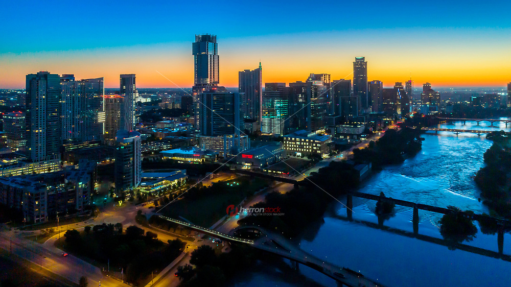 Aerial image as dawn looms over the horizon of the Austin Skyline and Lady Bird Lake as the sunrise peaks over the every growing cityscape in downtown Austin, Texas.