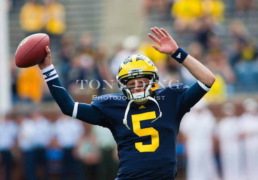 Michigan quarterback Tate Forcier (5) waves his arms in the air to music playing in Michigan Stadium, during warmups before an NCAA college football game with Connecticut, Saturday, Sept. 4, 2010, in Ann Arbor, Mich. (AP Photo/Tony Ding)
