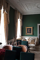 Rows of chairs of different periods and styles collect in the drawing room in which restoration has commenced