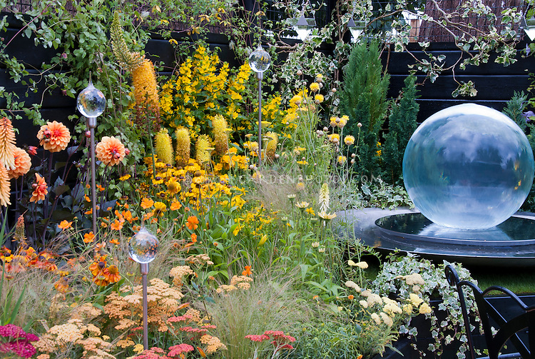 Yellow and orange color theme garden with glass globe ornament, glass gazing ball, glass flowers