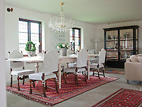 The elegant dining table has been reproduced in the style of the 1800s, while the chairs are covered in a linen fabric