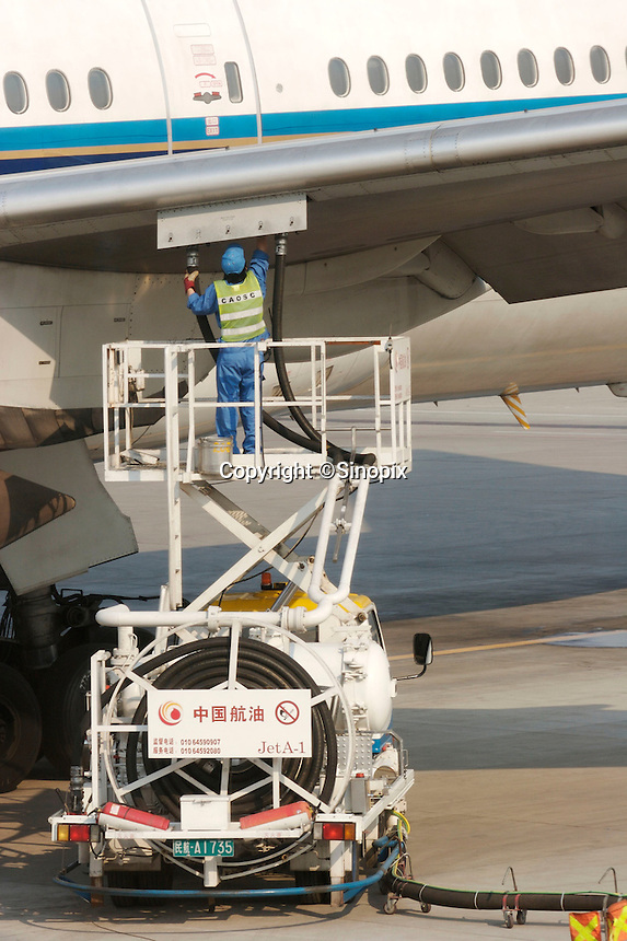 A worker of the China Aviation Oil Supply Corporation refuels a jet plane in the Beijing International Airport, Beijing, China..