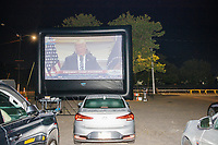 """US President Donald Trump is seen on a screen as people gathered to watch the 2020 Democratic National Convention at a """"Ridin' with Biden"""" Drive-In Theater viewing event at Suffolk Downs in Boston, Massachusetts, on Wed., Aug. 19, 2020."""