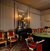 The walls and tented ceiling of the Council Room are covered in striped fabric and punctuated with spears