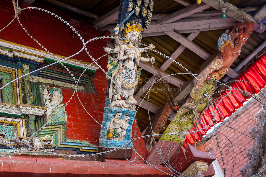 Nepal, Kathmandu.  Temple Carvings Dedicated to Shiva and Parvati, Barbed Wire to Prevent Theft.