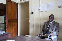 Detective Patrick Simiyu speaking to the prosecutor at the Nairobi Law Courts about a pending case.