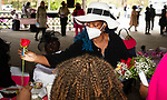 WATERBURY, CT 050821JS13—Patricia Sands, a member of the Black Women United Committee, hands out roses to all the ladies in attendance during a Mother's Day celebration held Saturday at Lakewood Park in Waterbury. Jim Shannon Republican American