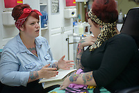 Brie Felts discusses tattoo designs with Valerie Gunther at Primal Instinct Tattoo. Photo by James R. Evans