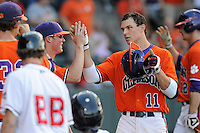 Third baseman Shane Kennedy (11) of the Clemson Tigers, right, is congratulated after hitting a home run in a game against the Furman Paladins on Wednesday, May 8, 2013, at Fluor Field at the West End in Greenville, South Carolina. (Tom Priddy/Four Seam Images)