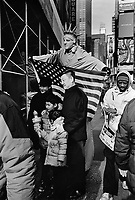 USA. New York City. Times Square. An artist is performing in the street of Midtown Manhattan as the Statue of Liberty holding an american flag. The performer is posing for a picture with a chinese tourist family. 21.01.2016 © 2016 Didier Ruef