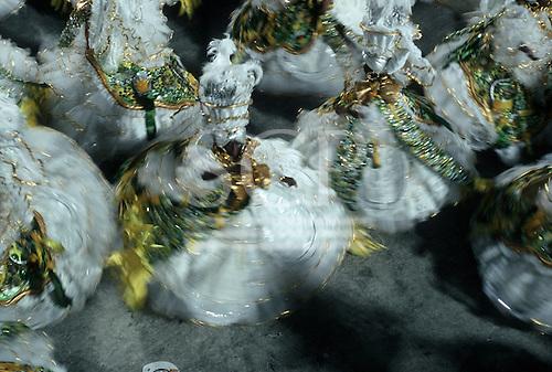 Rio de Janeiro, Brazil. Women in full swirling white and gold samba school costumes dancing in formation.