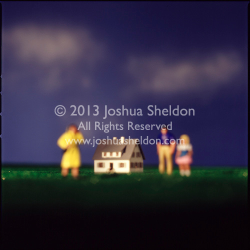Miniature family in front of house