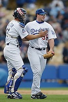 Chad Kreuter  and Eric Gange of the Los Angeles Dodgers celebrate  during a 2002 MLB season game at Dodger Stadium, in Los Angeles, California. (Larry Goren/Four Seam Images)