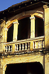 Weathered decaying arched facade and balcony of old French colonial building in the centre of Kampot, Cambodia.