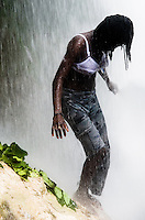 A Haitian girl performs a bathing and cleaning ritual under the waterfall during the annual religious pilgrimage in Saut d'Eau, Haiti, July 16, 2008. Every year in summer thousands of pilgrims from all over Haiti make the religious journey to the Saut d'Eau waterfall (100km north of Port-au-Prince). It is believed that 150 years ago the spirit of Virgin Mary (Our Lady of Mount Carmel) has appeared on a palm tree close to the waterfall. This place became a main pilgrimage site in Haiti since then. Haitians wearing only underwear perform a bathing and cleaning ritual under the 100-foot-high waterfall. Voodoo followers (many Haitians practise both voodoo and catholicism) hope that Erzulie Dantor, the Voodoo spirit of water, manifest itself and they get possessed for a short moment, touched by her presence.