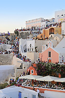 People on roofs and streets of Oia watch Santorini sunset