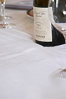 A bottle of Jacquesson Grand Vin Signature Extra Brut Millesimee vintage 1995 on a white table cloth and a wine glass in the foreground, Champagne Jacquesson in Dizy, Vallee de la Marne, Champagne, Marne, Ardennes, France, low light grainy grain
