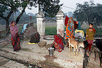 Villagers gather around a well in the middle of the village. Wells have been sunk deep into the ground but it is feared that the severe pollution has penetrated the groundwater, allowing many harm toxins to enter the water and food chain.