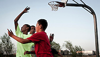 Children of migrant workers, who have come to Garden City to work at the Tyson meat packing plant, play basketball in a park where they live. The Tyson facility kills and processes between five and six thousand beef cattle every day. Kansas dominates the American beef industry, producing 25% of all beef raised in the USA. However, the industry is heavily dependent on cheap immigrant labour.