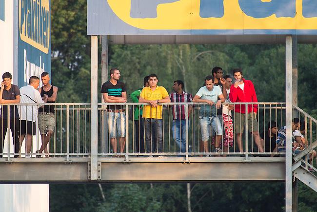"""Nach den pogromartigen Ausschreitungen gegen eine Fluechtlinsunterkunft im saechschen Heidenau am Freitag den 21. August 2015 durch Anwohnerinnen der Ortschaft, kamen am Samstag de 22. August 2015 ca. 250 Menschen in die Ortschaft um ihre Solidaritaet mit den Gefluechteten zu zeigen.<br /> Am Vorabend hatten Rassisten, Nazis und Hooligans sich zum Teil Strassenschlachten mit der Polizei geliefert um zu verhindern, dass Fluechtlinge in einen umgebauten Baumarkt einziehen. Ueber 30 Polizisten wurden dabei verletzt.<br /> Bis in die Abendstunden des 22. August blieb es trotz spuerbarer Anspannung um die Unterkunft ruhig. Im Laufe des Tages wurden immer wieder Gefluechtete mit Reisebussen gebracht was von den wartenenden Heidenauern mit Buh-Rufen begleitet wurde. Vereinzelt wurde auch """"Sieg Heil"""" gerufen, was die Polizei jedoch nicht verfolgte.<br /> Kurz vor 23 Uhr griffen Nazis und Hooligans dann wie am Vorabend die Polizei mit Steinen, Flaschen, Feuerwerkskoerpern und Baustellenmaterial an. Die Polizei mussten mehrfach den Rueckzug antreten, scheuchte den Mob dann von der Fluechtlingsunterkunft weg. Dabei wurden auch wieder Traenengasgranaten verschossen. Mindestens ein Nazi wurde festgenommen.<br /> Im Bild: Gefluechtete auf dem Gelaende des ehemaligen Baumarktes.<br /> 22.8.2015, Heidenau<br /> Copyright: Christian-Ditsch.de<br /> [Inhaltsveraendernde Manipulation des Fotos nur nach ausdruecklicher Genehmigung des Fotografen. Vereinbarungen ueber Abtretung von Persoenlichkeitsrechten/Model Release der abgebildeten Person/Personen liegen nicht vor. NO MODEL RELEASE! Nur fuer Redaktionelle Zwecke. Don't publish without copyright Christian-Ditsch.de, Veroeffentlichung nur mit Fotografennennung, sowie gegen Honorar, MwSt. und Beleg. Konto: I N G - D i B a, IBAN DE58500105175400192269, BIC INGDDEFFXXX, Kontakt: post@christian-ditsch.de<br /> Bei der Bearbeitung der Dateiinformationen darf die Urheberkennzeichnung in den EXIF- und IPTC-Daten nicht entfernt werden, diese """
