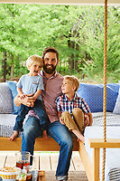 Josh McCullock and his sons on the swinging L-shaped porch bed.