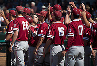LOS ANGELES, CA - April 10, 2011: Dave Giuliani of Stanford baseball enters the dugout to high-fives after scoring during Stanford's game against USC at Dedeaux Field in Los Angeles. Stanford lost 6-2.